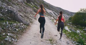 Taking video from the back in amazing landscape place at nature running young women with a good looking fit bodies