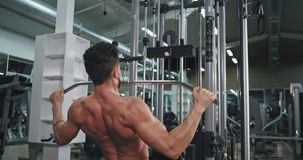 Taking video from the back bodybuilding man exercises at gym class concentrated doing well the exercises. 4k stock footage
