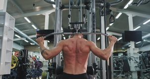 Taking video from the back young guy exercises hard on his gym class bodybuilding concept. 4k stock video