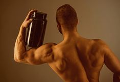 Taking vitamins for a healthy diet. Muscular man with vitamin supplements. Strong man hold supplement bottle. Bodybuilding sport and fitness. Vitamin diet and stock photography