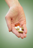 Taking daily vitamins or supplements. Hand holding daily supplements, vitamins or medication on green background Stock Photo