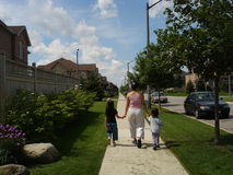 Taking a walk. Young mother walks around a city block with her two children Royalty Free Stock Photo