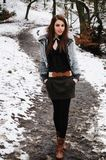 Taking a walk. Female walking down a path in the woods with snow covering the sides Royalty Free Stock Images
