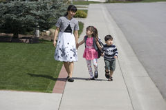 Taking a walk. A mother and her two children walking on the sidewalk Royalty Free Stock Images