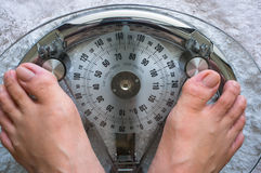 Taking weight. Photo showing two feet on a modern analog scale taking weight Royalty Free Stock Image