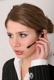 Taking your call. Pretty young woman in business attire talking on a headset Stock Photo