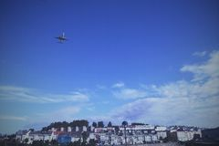 TakingoffPlane. Taking Off plane over houses in a blue skye an white clouds Stock Photography