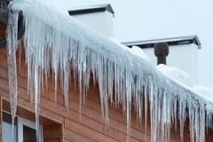 Taklägga av huset med snow och istappar arkivbilder