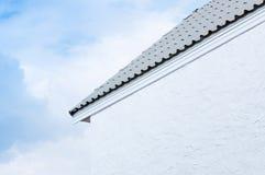 Taklägga takfot och den vita väggen på bakgrund för blå himmel arkivfoton