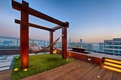Taklägga terrassen med hängmattan på en solig dag Arkivbild
