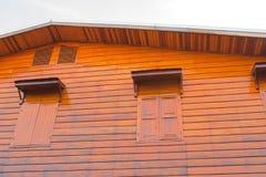 Taklade trähus och gult fönster Arkivbild