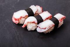 Tako nigiri sushi. Close-up of Tako nigiri sushi with cooked octopus on a black slate background Royalty Free Stock Image