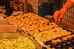 Takoyaki étant fait cuire dans une stalle de nourriture la nuit photographie stock libre de droits