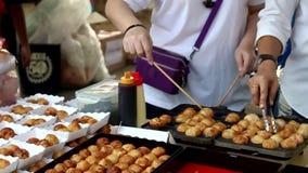 Takoyaki cooking on hot pan. People grilling takoyaki for serve customer stock video footage
