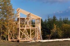 Takstrålar Solig höstlig afton på konstruktionsplatsen av ett trähus oavslutat hus arkivbilder