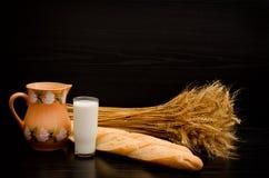 Taktpinnar en kanna, ett exponeringsglas av mjölkar och en kärve på en svart bakgrund Arkivfoton