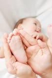 Talón de los pequeños niños en las manos de su madre Imagen de archivo