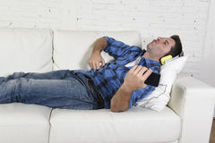 20-tal eller 30-talman som har gyckel som ligger på soffan som lyssnar till musik på mobiltelefonen med hörlurar som spelar Air G Fotografering för Bildbyråer