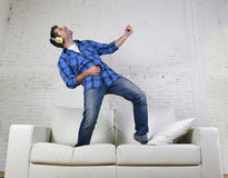 20-tal eller 30-talmannen hoppade på soffan som lyssnar till musik på mobiltelefonen med hörlurar som spelar Air Guitar Royaltyfri Bild