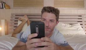 30-tal för ung man eller lyckligt ligga för 40-tal på säng hemma i morgonen genom att använda mobiltelefonen som kontrollerar soc Royaltyfria Foton