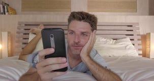 30-tal för ung man eller lyckligt ligga för 40-tal på säng hemma i morgonen genom att använda mobiltelefonen som kontrollerar soc Royaltyfria Bilder
