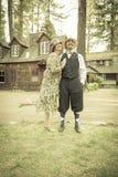 20-tal klädde romantiska par framme av den gamla kabinen Arkivbild