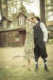 20-tal klädde romantiska par framme av den gamla kabinen Arkivfoto