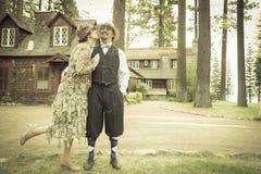 20-tal klädde romantiska par framme av den gamla kabinen Arkivbilder