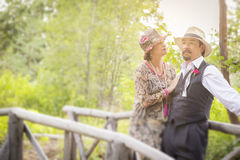 20-tal klädde romantiska par på träbron Arkivbild