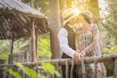 20-tal klädde romantiska par som kysser i en skogsbevuxen skog Royaltyfria Foton