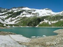 Tal und See in den Alpen Stockfotografie