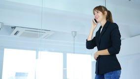 Tala på telefonen som ser till och med fönster, baksidasikt Fotografering för Bildbyråer