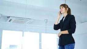 Tala på telefonen, ung kvinnlig som ser till och med fönster Royaltyfri Bild