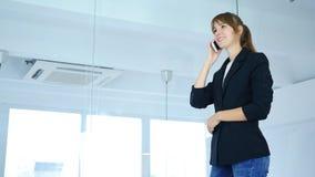 Tala på telefonen, ung kvinnlig som ser till och med fönstret, sidosikt Royaltyfria Bilder