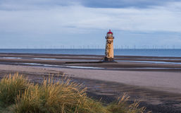 Talacre Lighthouse, Flintshire. Talacre Lighthouse, North Wales in morning light, with coastal grasses in the foreground and wind turbines on the horizon Stock Photography