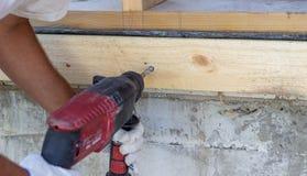 Taladro del trabajo Construcci?n de casas de madera Las manos de los hombres en guantes de la construcci?n foto de archivo