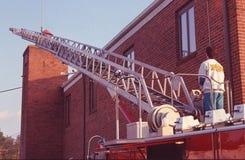 Taladros del bombero en uso de la escalera con el camión de escalera imagen de archivo