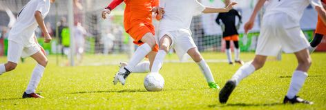 Taladros del fútbol del ` s de los niños Niños que golpean el partido de fútbol con el pie en echada Fotos de archivo