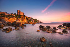 Talamone rock beach and medieval fortress at sunset. Maremma Arg Royalty Free Stock Photography
