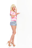 Talande blond flicka som pekar på det vita stora banret Arkivbild
