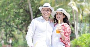 Talande drink Juice Under Palm Trees för par, lycklig man och turist- kommunikation för kvinna på tropisk semester arkivfilmer
