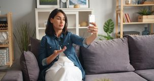 Talande göra en gest för olycklig flicka göra online-video appell med smartphonen hemma arkivfilmer