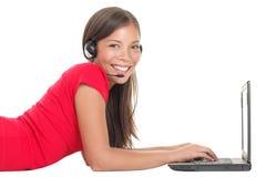 talande kvinna för hörlurar med mikrofonbärbar dator royaltyfri bild