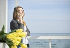 talande kvinna för lycklig telefon arkivfoto