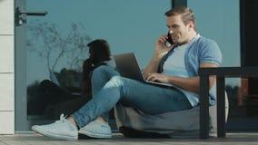 Talande mobil för säker man och användabärbar dator Modern arbetare som skriver på bärbara datorn stock video