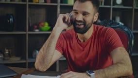Talande mobiltelefon för lycklig affärsman i hem- arbetsplats Två gladlynta affärsmän som talar om affär medan en av dem som peka arkivfilmer
