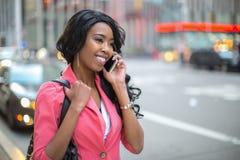 Talande mobiltelefon för svart afrikansk amerikankvinna i stad Royaltyfri Foto