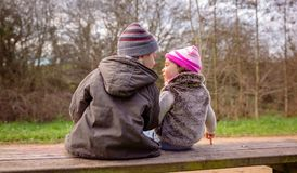 Talande sammanträde för pojke och för liten flicka på en bänk arkivfoto