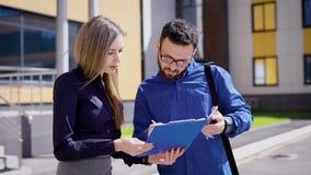 Talande telefon för affärsman och undertecknande legitimationshandlingar Upptaget chefanseende på kontorsbyggnad med partnern och stock video
