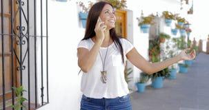 Talande telefon för gladlynt kvinna på gatan Arkivfoton